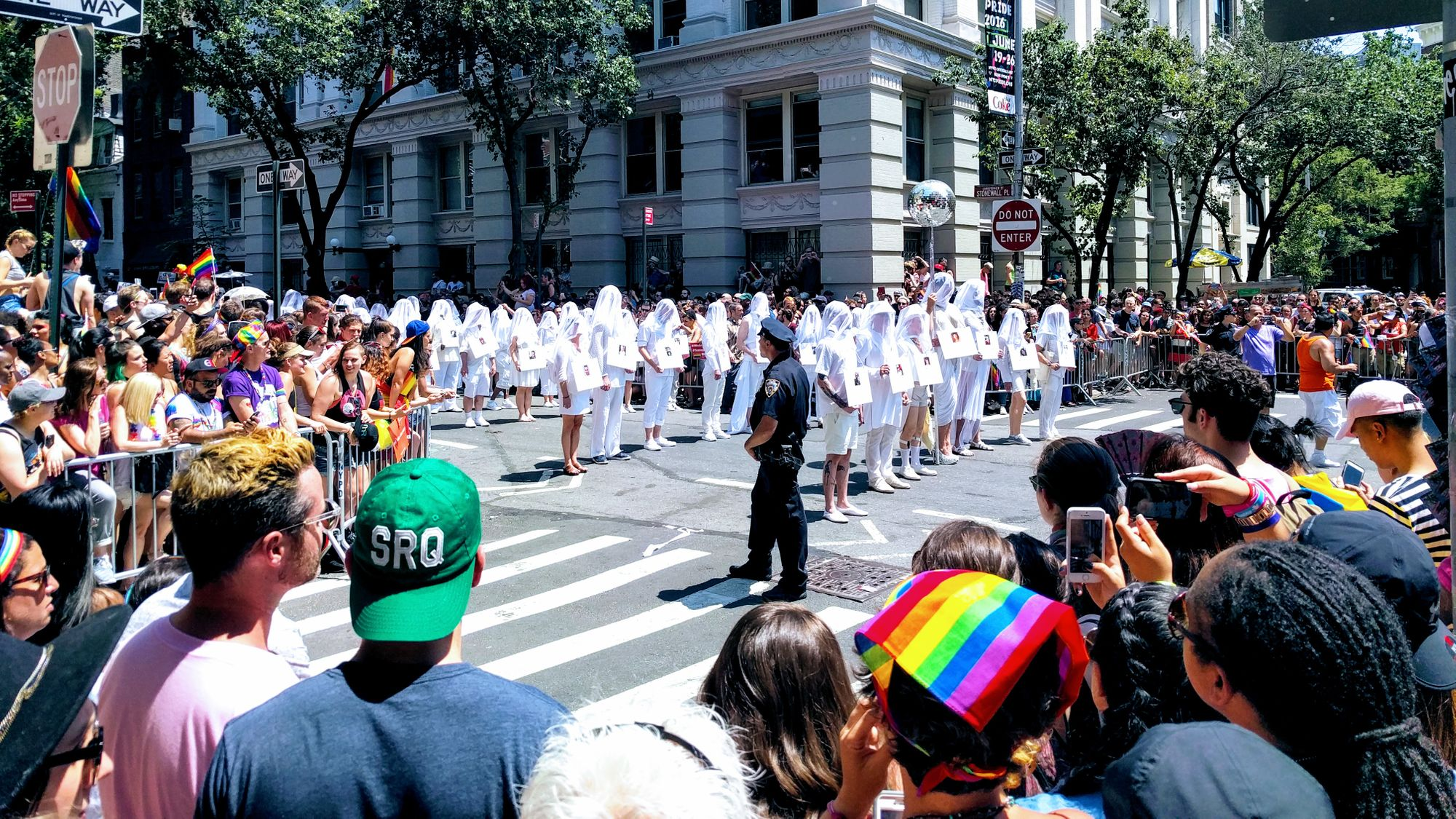 A crowd of people, many rainbow flags among them, look on the parade at an intersection. Rows of people dressed in white with shrouds stand in the intersection, each one representing someone killed in the Pulse shooting.