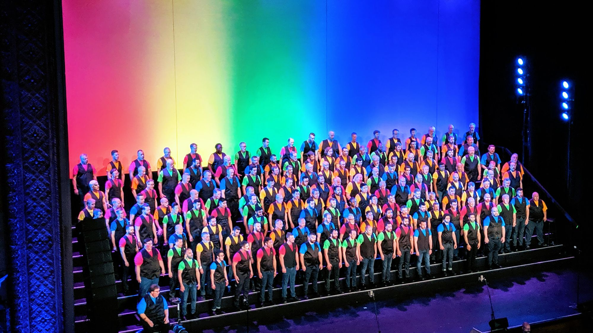 A chorus of men dressed in alternating brightly colored t-shirts with black vests stand on stage with a gradient rainbow background behind them.
