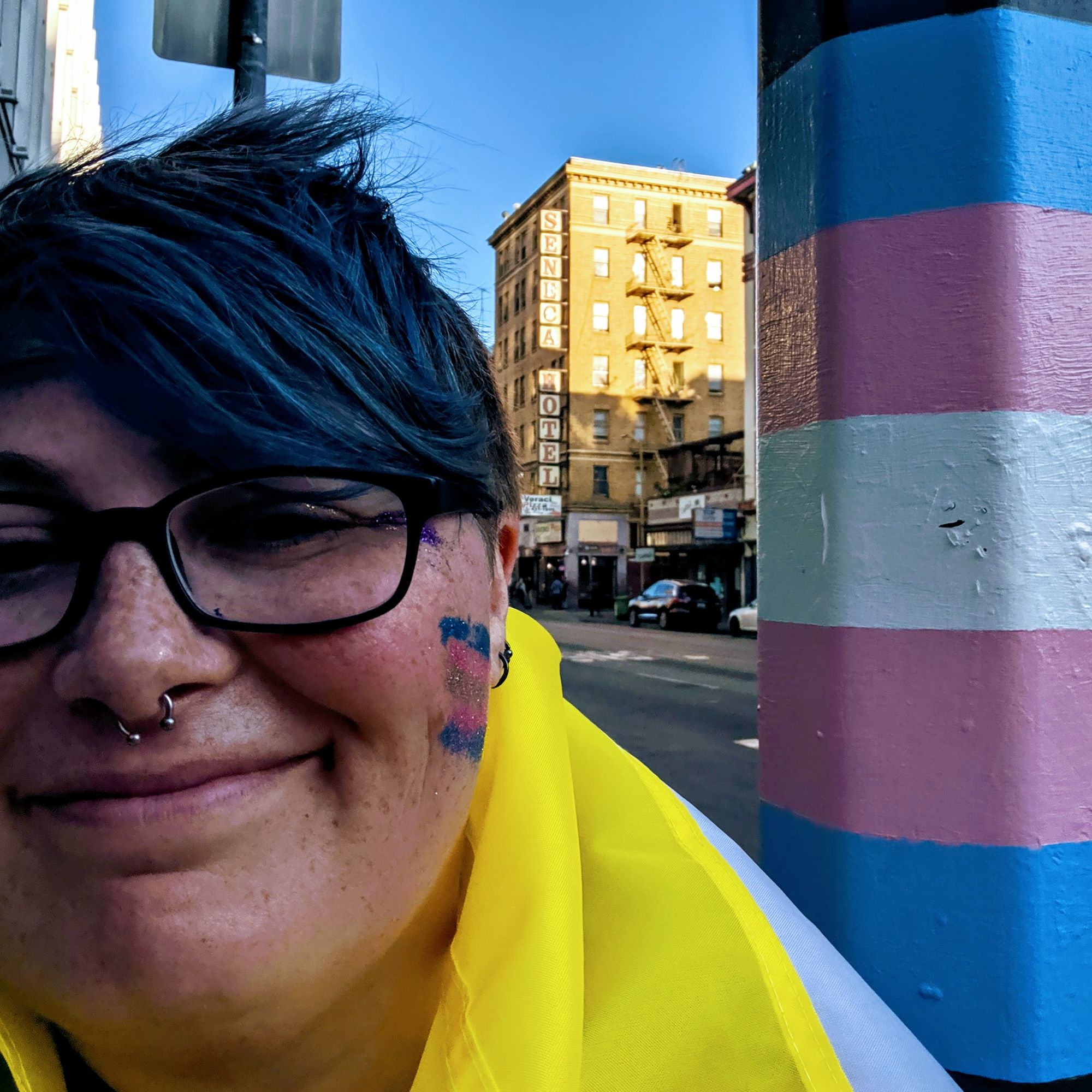 Reid is smiling and standing next to a light pole in San Francisco's Tenderloin that has a trans flag painted on it. They are smiling, have a glitter trans flag painted on their cheek, and a non-binary pride flag wrapped around their shoulders.