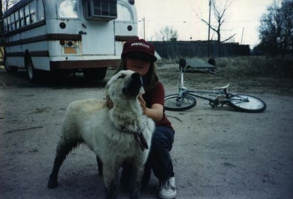 Reid is 6-years-old and crouched down with a dirty white dog. An old school bus and bicycle can be seen in the background.